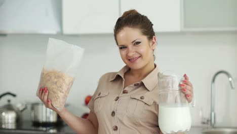 Woman-Standing-In-Kitchen-With-Cornflakes-And-Milk