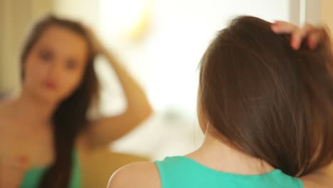 Young-Woman-Looking-At-Camera-And-Straightens-Hair