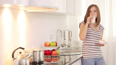 Young-Woman-Standing-In-Kitchen-And-Drinking-Milk-With-Cornflakes