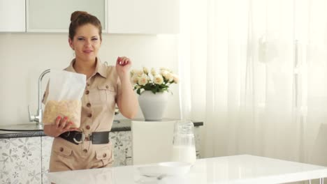 Young-Woman-Standing-In-Kitchen-And-Eating-Cornflakes