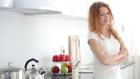 Attractive-Young-Woman-In-Kitchen-Drinking-Milk-From-Glass-And-Smiling