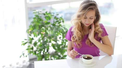 Attractive-Young-Woman-Sitting-At-Table-With-Green-Plant-On-Background-Drinking