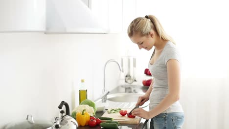 Attractive-Young-Woman-Standing-At-Kitchen-Table-Cutting-Tomatoes-Looking