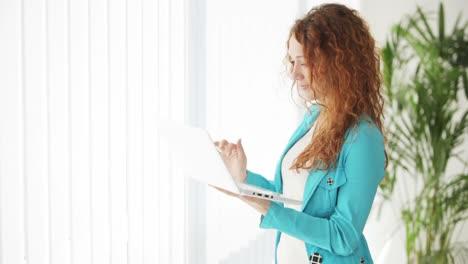 Atractiva-Mujer-Joven-De-Pie-Delante-De-La-Ventana-Usando-Laptop-Y-Sonriendo