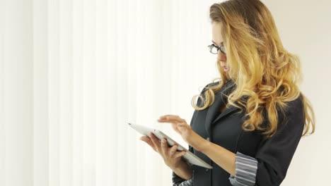 Joven-Atractiva-Con-Gafas-Con-Touchpad-Y-Mirando-A-Cámara