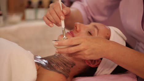 Beautician-Applying-Cosmetic-Mask-On-Woman\-s-Face-At-Beauty-Salon-Panning