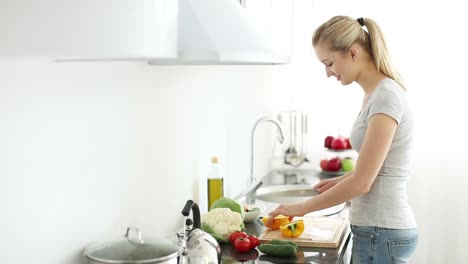 Beautiful-Young-Woman-Cutting-Bell-Peppers-On-Cutting-Board-In-Kitchen