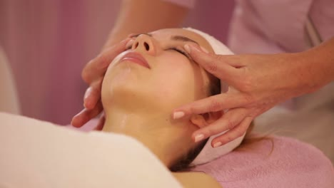 Beauty-Specialist-Massaging-Female-Face-At-Beauty-Salon