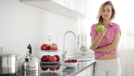 Blond-Girl-Standing-In-Kitchen-Holding-Apple-And-Smiling-At-Camera