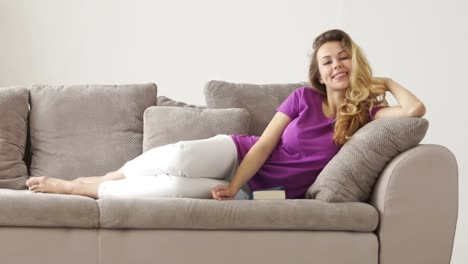 Cute-Girl-Lying-On-Couch-Laughing-And-Smiling-At-Camera