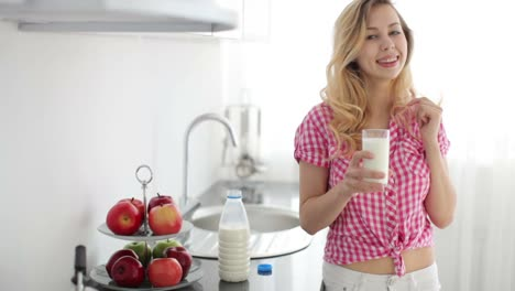 Cute-Girl-Standing-In-Kitchen-Drinking-Milk-And-Laughing-At-Camera