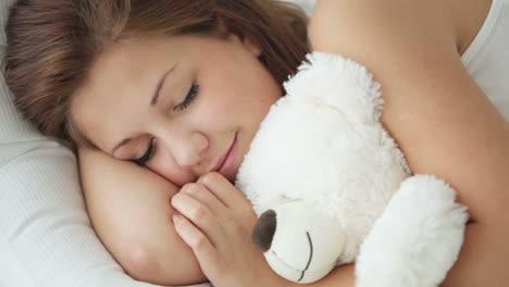 Cute-Sleeping-Girl-Hugging-Teddy-Bear-And-Smiling