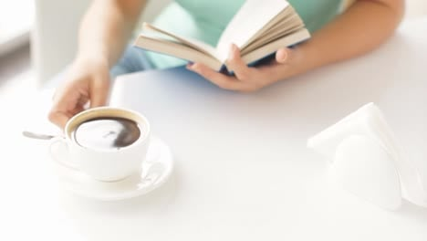 Girl-Holding-Bluecovered-Book-With-Cup-Of-Coffee-On-Foreground