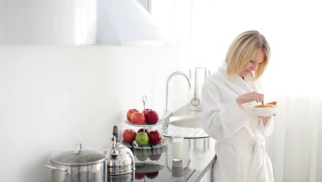Girl-In-Bathrobe-Eating-Cereal-And-Smiling