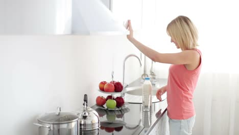 Girl-Standing-In-Kitchen-And-Pours-Glass-Of-Milk-01