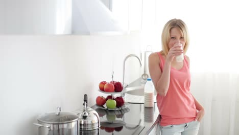 Girl-Standing-In-Kitchen-Drinking-Milk-With-Smile