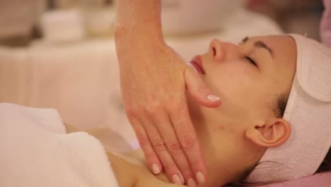 Massage-Specialist-Applying-Moisturiser-On-Female-Face-Panning-Camera