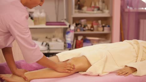 Massage-Specialist-Massage-Of-Woman\-s-Legs-At-Beauty-Salon-Panning-Camera