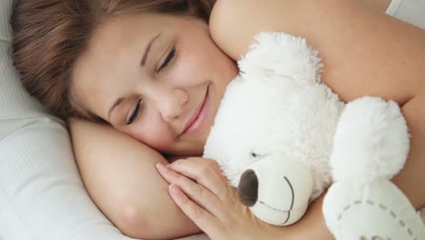Pretty-Girl-In-Bed-Hugging-Teddy-Bear-And-Smiling-At-Camera