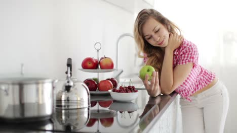 Pretty-Girl-In-Kitchen-Holding-Green-Apple-And-Looking-At-Camera-With-Smile