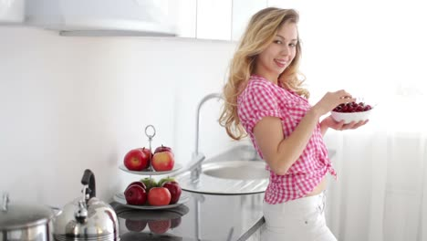 Pretty-Girl-Standing-In-Kitchen-Eating-Cherries-And-Smiling-At-Camera