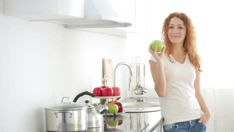 Pretty-Girl-Standing-In-Kitchen-Holding-Green-Apple-And-Smiling-At-Camera