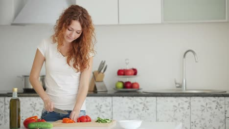 Pretty-Young-Woman-Cutting-Vegetables-In-Kitchen-With-Smile
