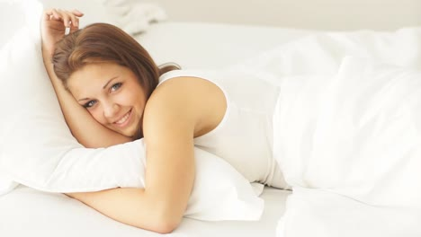 Pretty-Young-Woman-Lying-In-Bed-And-Smiling-At-Camera