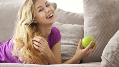 Pretty-Young-Woman-On-Sofa-Holding-Apple-Smiling-At-Laughing-At-Camera