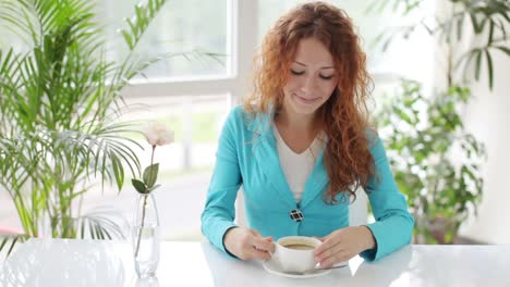 Pretty-Young-Woman-Sitting-At-Table-Drinking-Coffee-And-Smiling