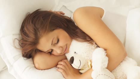 Pretty-Young-Woman-Sleeping-In-Bed-Hugging-Teddy-Bear-Waking-Up-And-Smiling