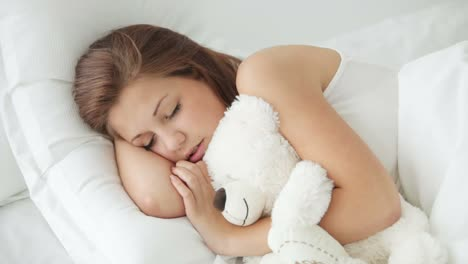 Pretty-Young-Woman-Sleeping-With-Teddy-Bear-Waking-Up-And-Smiling