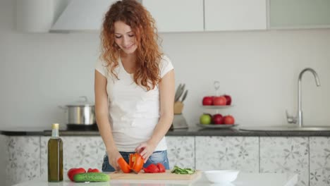 Pretty-Young-Woman-Standing-In-Kitchen-Cutting-Vegetables-And-Smiling-At-Came