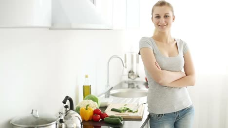 Pretty-Young-Woman-Standing-In-Kitchen-Cutting-Vegetables-Turning-Around
