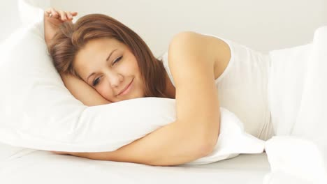 Relaxed-Pretty-Girl-Lying-In-Bed-Smiling-And-Laughing-At-Camera