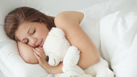 Sleeping-Young-Woman-Hugging-Teddy-Bear-Opening-Eyes-And-Smiling-At-Camera