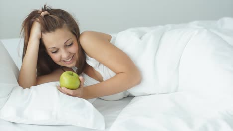 Smiling-Girl-Lying-In-Bed-Holding-Green-Apple-Laughing-At-Camera