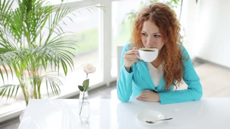Smiling-Young-Woman-Sitting-At-Table-Drinking-Coffee-And-Looking-At-Camera