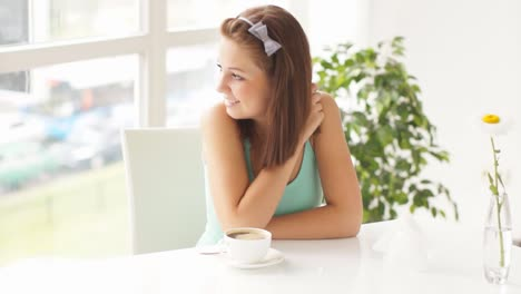 Smiling-Young-Woman-Sitting-At-Table-Stirring-Coffee-And-Laughing-At-Camera