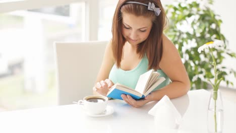 Smiling-Young-Woman-Sitting-At-Table-Stirring-Coffee-Reading-Bluecovered-Book