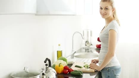 Smiling-Young-Woman-Standing-At-Kitchen-Table-Cutting-Cucumbers
