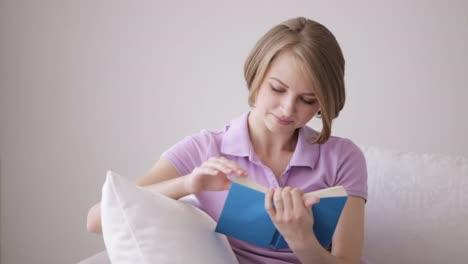 Mujer-Joven-Pensativa-Que-Se-Relaja-En-El-Sofá-Y-Leyendo-El-Libro
