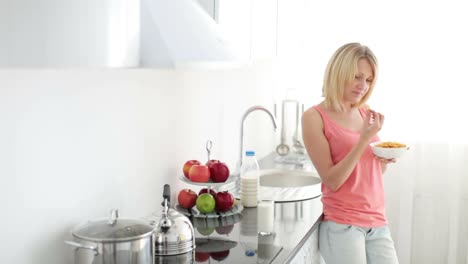 Woman-Standing-In-Kitchen-And-Eating-Cornflakes