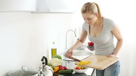 Junge-Frau-In-Der-Küche-Die-Frisch-Geschnittene-Paprika-In-Den-Salat-Gibt