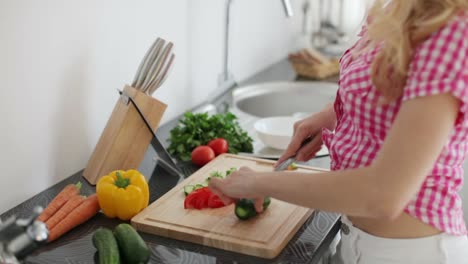 Young-Woman-In-Kitchen-Chopping-Vegetables