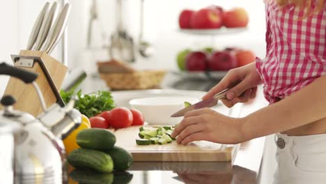 Young-Woman-In-Kitchen-Cutting-Vegetables-On-Cutting-Board