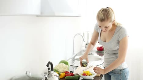 Young-Woman-In-Kitchen-Dressing-Vegetable-Salad-With-Olive-Oil-And-Smiling