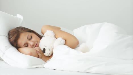 Junge-Frau-Liegt-Im-Bett-Und-Umarmt-Teddybär-Lächelnd-In-Die-Kamera