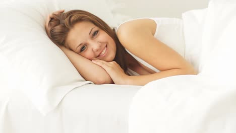 Young-Woman-Lying-In-Bed-Smiling-At-Camera-Closing-Eyes-And-Falling-Asleep
