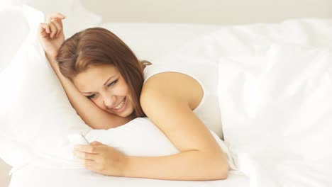 Young-Woman-Lying-In-Bed-Using-Mobile-Phone-Before-Falling-Asleep